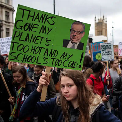Girl holding sign reading 'Thanks Gove*, My planet's too hot and my school's too cold'  at a rally