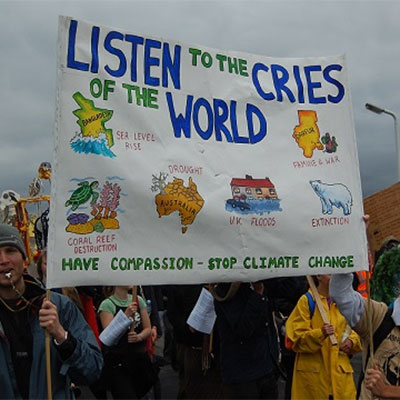 Protesters holding a sign that reads 'Listen to the cries of the world. Have compassion, stop climate change'