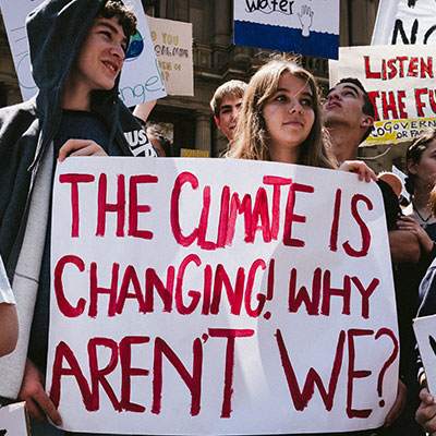 Protesters holding a sign reading 'The climate is changing, why aren't we?'