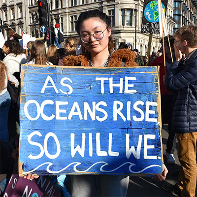 Protester holding a sign that reads 'As the oceans rise so will we'